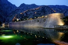 defensive fortress by the lake in night illumination