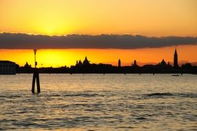 distant view from water to venice at sunset