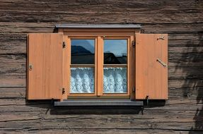 Window with wooden shutters in the house