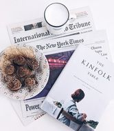 cookies on a plate, a cup of milk, newspapers and magazines on the table