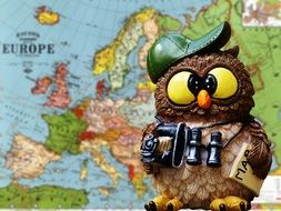 statuette of an owl on a background of a world map