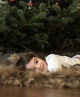 nice caucasian Child Girl lying on floor at christmas tree