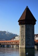 photo of a wooden bridge and tower in Switzerland