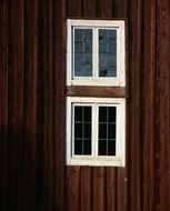 two white Windows in brown Wooden Facade