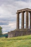 national monument of scotland on a green hill