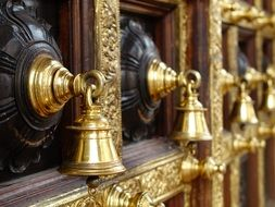 macro photo of golden bells in hindu temple
