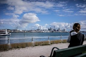 young girl sits on bench in view of harbor