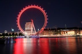 distant view of a ferris wheel in london in red night illumination