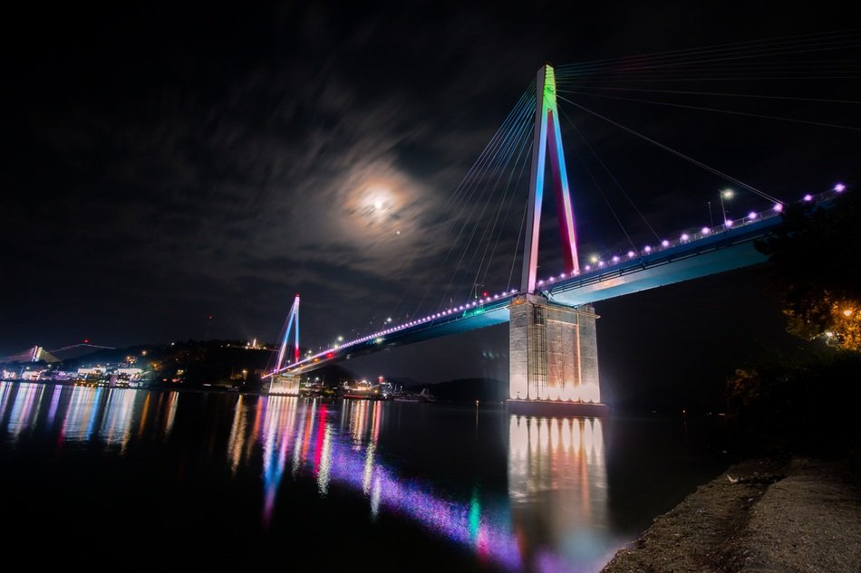 landscape of colorful bridge reflected in the water at night