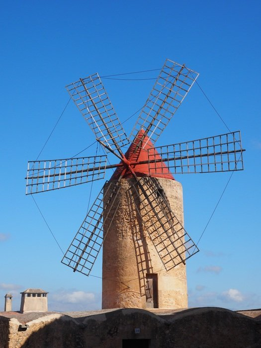windmill on a hill against a blue sky