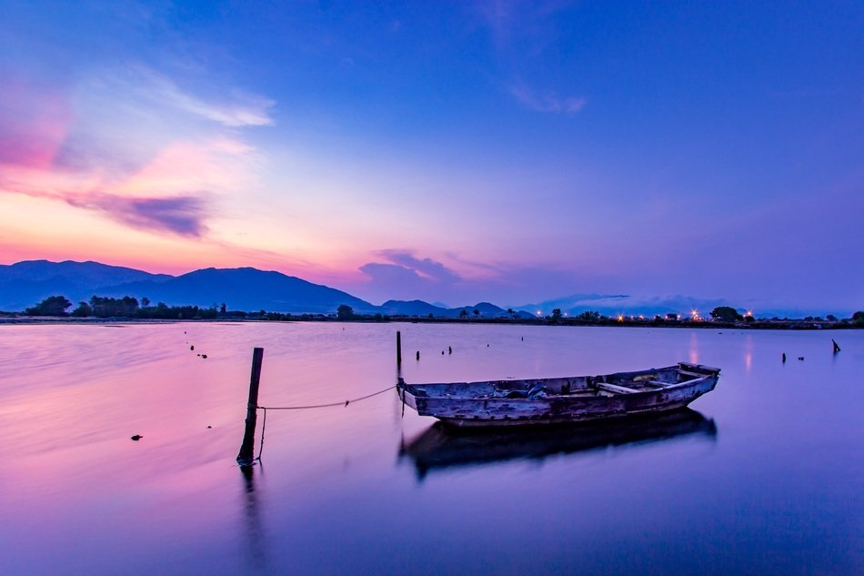 boat on the water against the background of colorful sunset