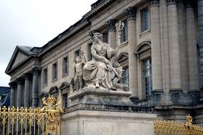 VersStatue of sitting woman with caduceus at golden fence of palace, france, versailles