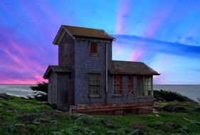 abandoned building by the sea on a background of colorful sunset