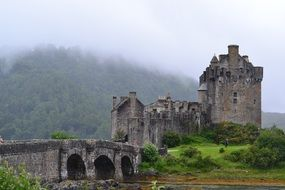 medieval Castle at foggy mountain, uk, Scotland