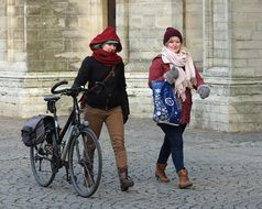 girlfriends are walking along the street with a bicycle