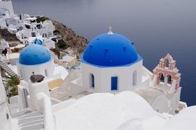 panoramic view of white buildings with blue domes in Santorini