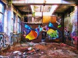 colorful drawings on the wall of an abandoned factory