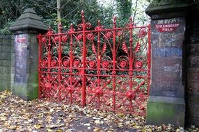 red painted wrought Iron Gate to strawberry field at fall, uk, england, liverpool