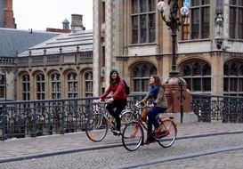 girls on bicycles ride a bridge