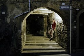 woman on stairs in a lighted tunnel