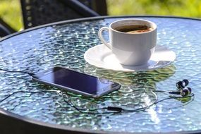 cup of coffee, headphones and a smartphone on a table in an outdoor cafe