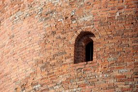 small arched Window in old red Brick Wall