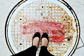 feet on the sewer hatch