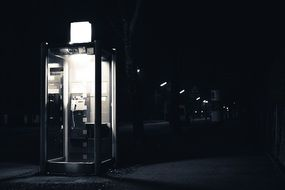 black and white photo of a telephone booth at night