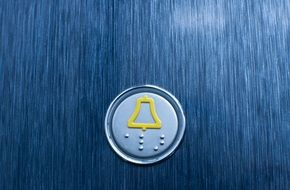 elevator button on a blue wall