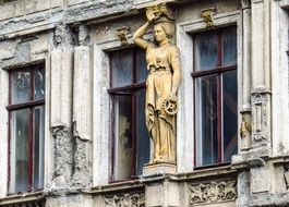 female statue on the facade of an old house