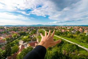 man\'s hand over green cityscape