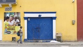 man walking along Old Colonial Building with blue gate, colombia, cartagena