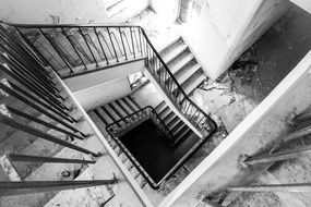 black and white picture of a staircase if an abandoned house