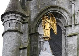 Golden angel statue and medieval church
