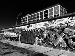 black and white photo of a wall with graffiti in Berlin
