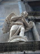 stone sculpture of an angel on the facade of the cathedral