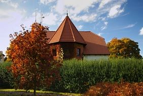 red brick building with tile roof in colorful autumn garden