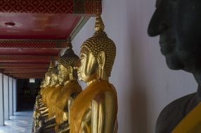 golden buddha statues in temple in Thailand