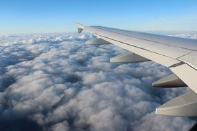 airplane wing over fluffy clouds window view
