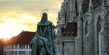 bronze statue in front of a gothic temple