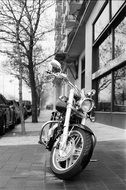 Black and white photo of motorbike on a street