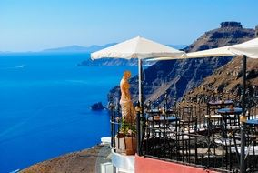 tables with chairs under umbrellas on the island of santorini