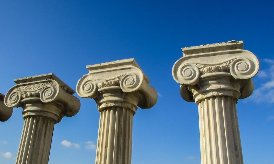 three greek columns against a blue sky