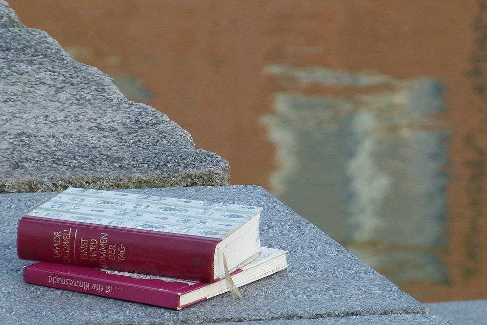 two closed books on stone wall at water