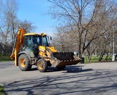 Yellow and black excavator on the road