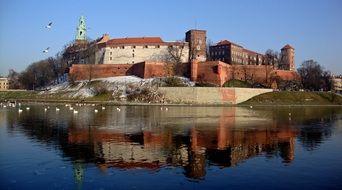 reflection of the castle in the water in Krakow