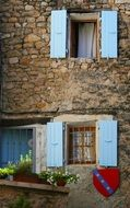 blue Open Shutters on facade of old stone building, France