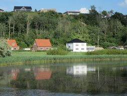 houses are reflected in the water on the picturesque shore