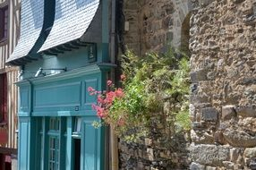 beautiful old house Facade with flowers on stone wall, france, brittany