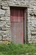 Red wooden door in old Stone wall